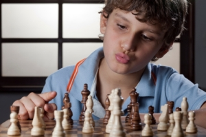 boy_playing_chess_thinking_how_to_make_a_move__1408739256